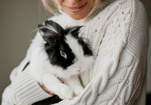 Женщина гладит очаровательный кролик Бесплатные Фотографии