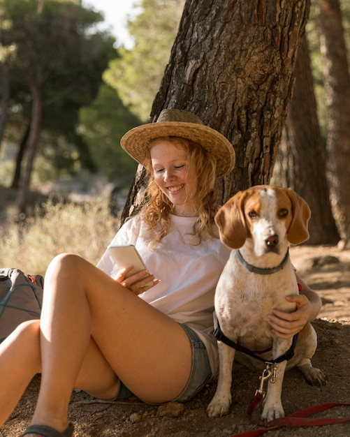 Женщина гладит свою милую собаку и использует ее мобильный телефон Premium Фотографии