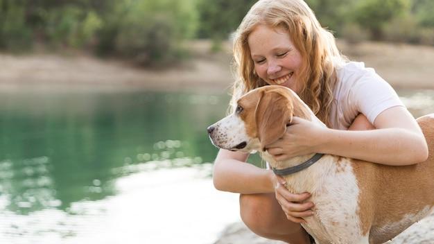 Женщина гладит свою собаку на берегу озера Бесплатные Фотографии