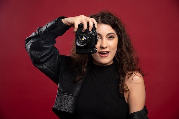 カメラで写真を撮るすべての黒い服の女性写真家。 無料写真
