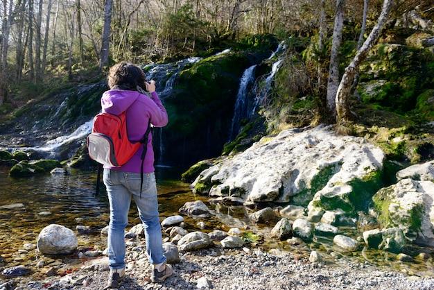 Женщина фотограф, фотографирующий водопад, осенью Premium Фотографии