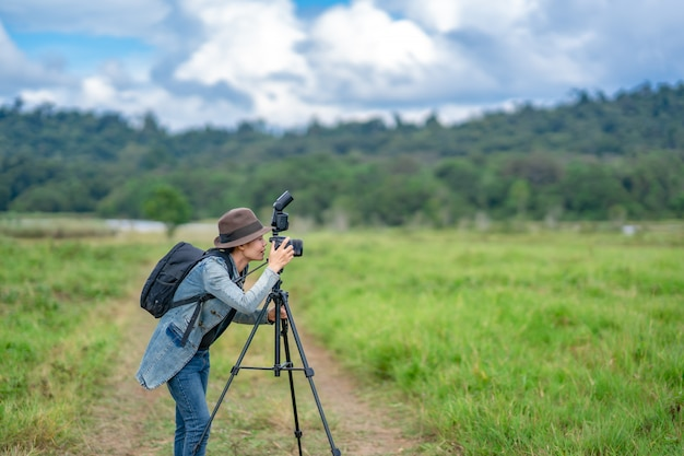 Woman photographer take photo on hills nature, she holding and looking camera. Premium Photo