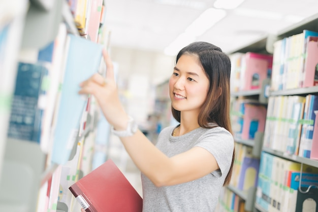 Woman pick a book from the bookshelf in library. Premium Photo