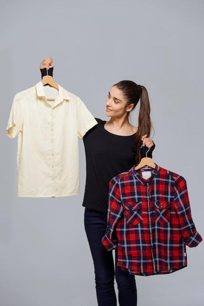 Женщина выбирает наряд, держа в руках две рубашки Бесплатные Фотографии