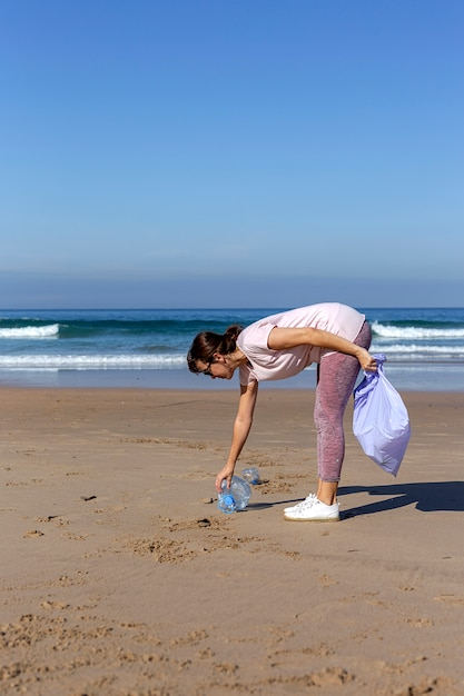 Woman picking up trash and plastics cleaning the beach Premium Photo