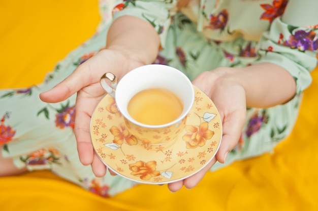 Woman on the picnic sits on the yellow cover and holds cup of tea. Premium Photo