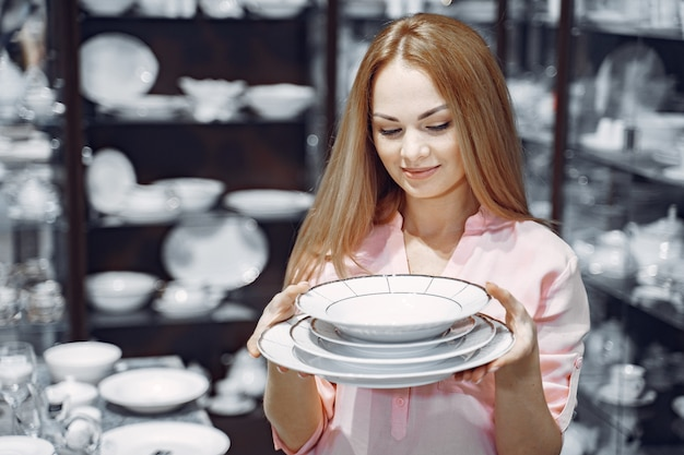 Woman in a pink blouse buys dishes in the store Free Photo