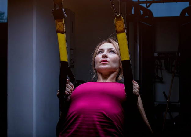 Woman in pink doing back training with back extention machine in a gym. Free Photo