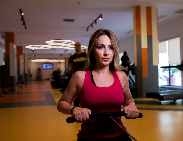 Woman in pink fitness outfit doing shoulder training in a gym. Free Photo