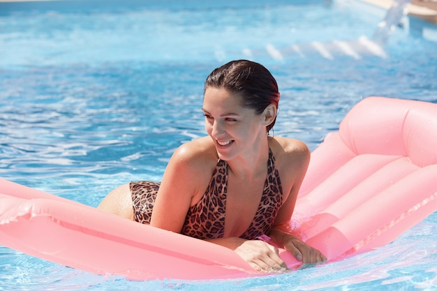 Woman on pink inflatable in swimming pool wearing swimming suit with leopard print, looking smiling aside Free Photo