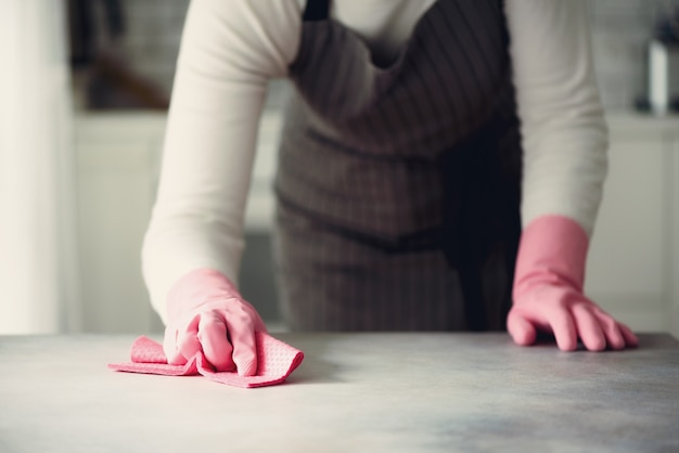 Woman in pink rubber protective gloves wiping dust and dirty. cleaning concept,, copy space Premium Photo