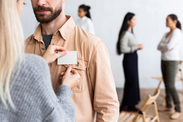 Donna che fissa l'etichetta del nome sulla camicia dell'uomo durante una sessione di terapia di gruppo Foto Gratuite