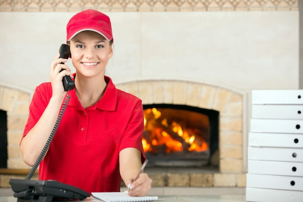 Woman of pizza holding pen and diary for placing order. Premium Photo