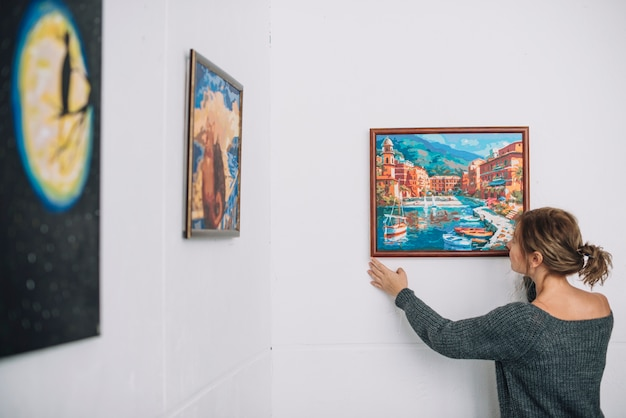 Woman placing painting on wall Free Photo