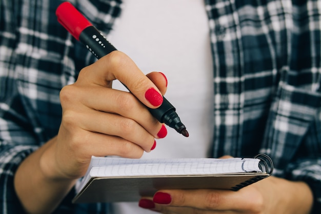 Woman in plaid shirt and red manicure felt pen writing in a notebook Premium Photo