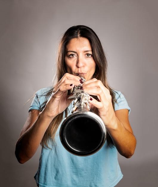 Женщина играет на кларнете на сером Premium Фотографии