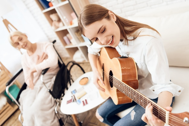 Woman playing guitar for old lady in wheelchair. Premium Photo