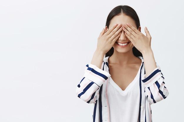 Donna che gioca a nascondino. emozionata bella donna elegante in camicetta a righe, che copre gli occhi con i palmi e sorride con espressione incuriosita, in attesa di sorpresa Foto Gratuite