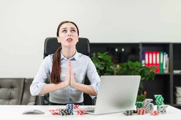 Woman playing online casino and poker via laptop in the office and praying to win Premium Photo