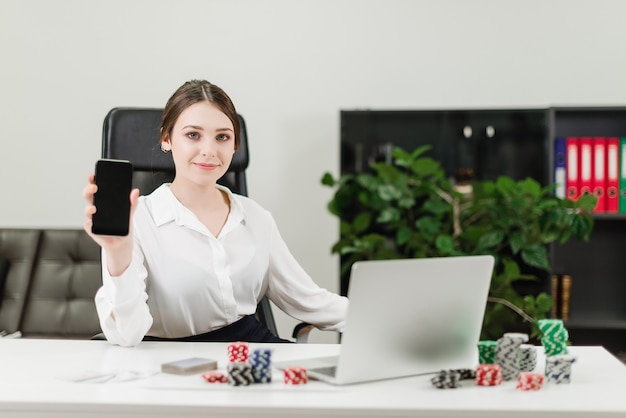 Woman playing online casino and poker via laptop in the office and showing blank phone screen Premium Photo