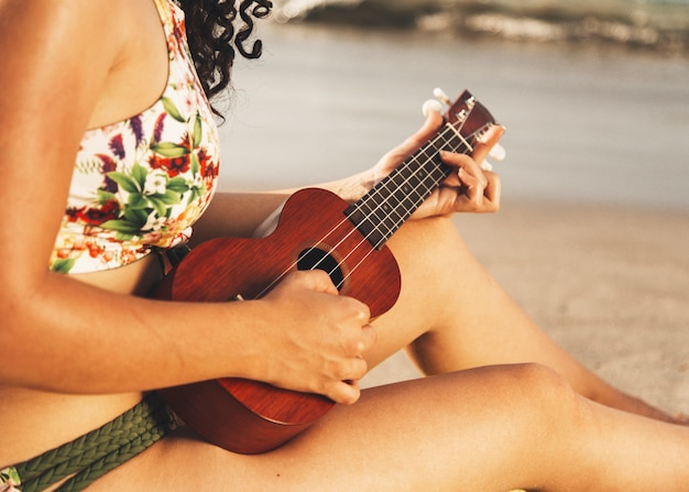 Woman playing ukulele on beach Free Photo