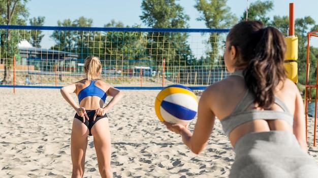 Donna che gioca a pallavolo e che fa segnali con la mano al compagno di squadra dietro Foto Gratuite