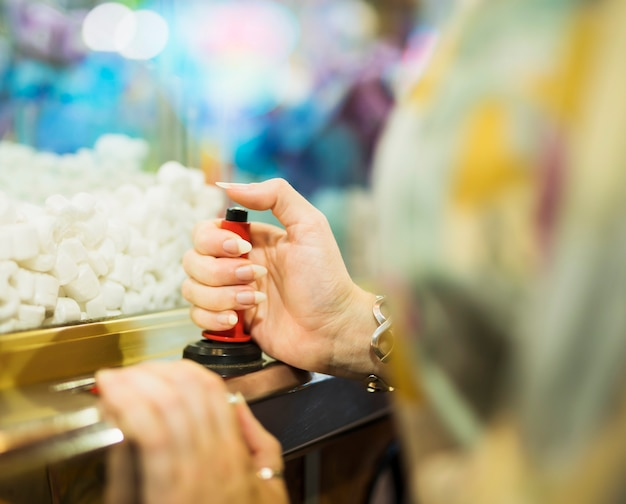Woman playing with claw machine Free Photo