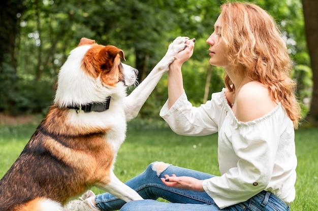 Donna che gioca con il suo migliore amico nel parco Foto Gratuite