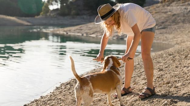 Женщина играет со своей собакой на берегу озера Бесплатные Фотографии