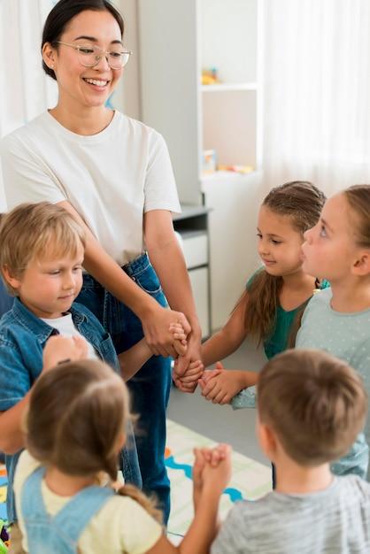 室内で生徒と遊ぶ女性 無料写真