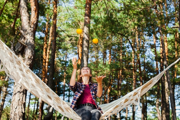 Woman playing with lemons in hammock Free Photo