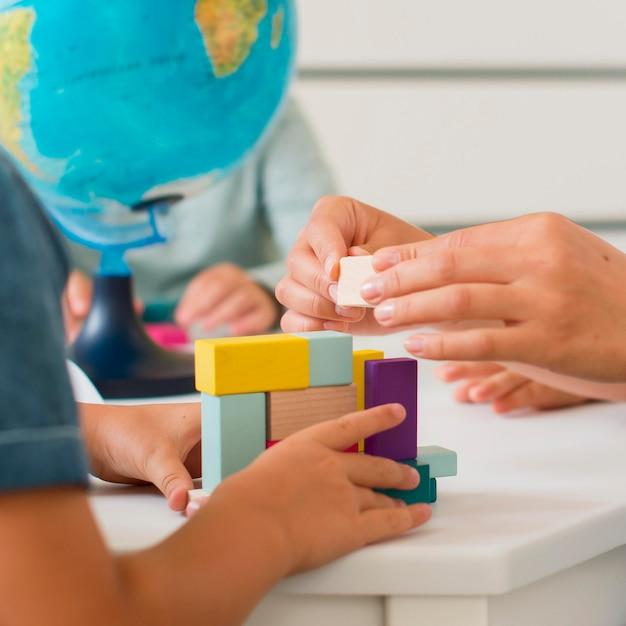 授業中に小さな子供たちと遊ぶ女性 Premium写真