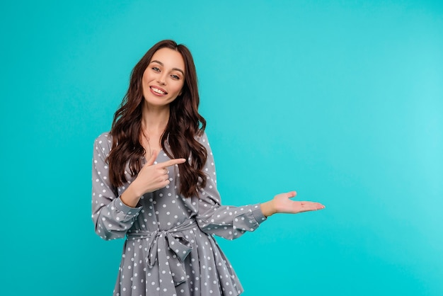 Woman pointing at copyspace at palm of hand isolated over bright blue background Premium Photo