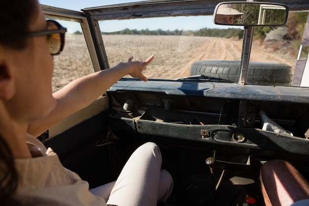 Woman pointing while traveling in vehicle Free Photo
