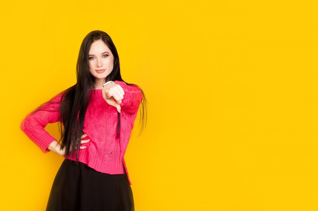 The woman points her finger at you, on a yellow wall, with copy space. concept motivational photos, who if not you, you should make your choice. Premium Photo
