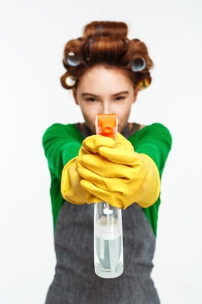 Женщина указывает спрей с желтыми перчатками на руках Бесплатные Фотографии