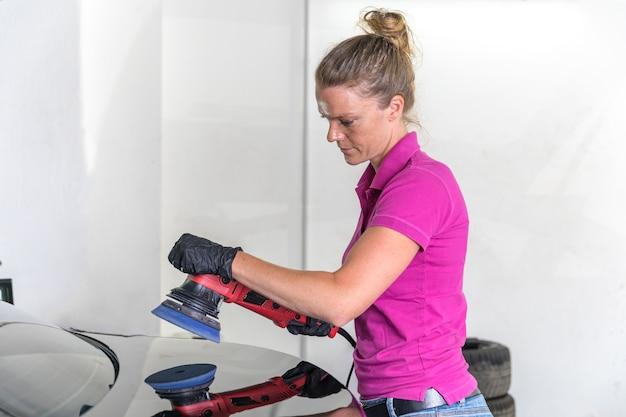 Женщина полирует кузов автомобиля в обслуживании. Premium Фотографии