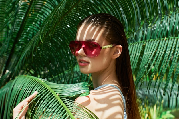 Woman portrait in glasses on a  of green leaves of palm trees, beautiful face Premium Photo