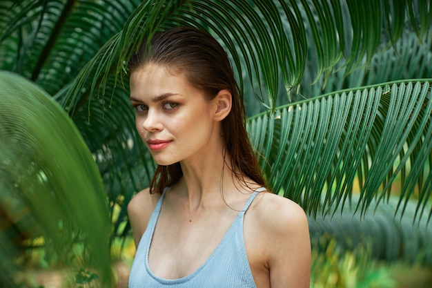 Woman portrait in glasses on a space of green leaves of palm trees, beautiful face Premium Photo