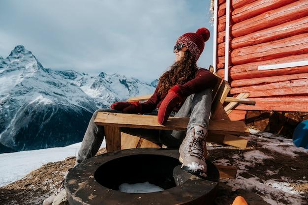 Женский портрет в солнечную погоду зимой в горах. девушка в теплой одежде крупным планом фото. Premium Фотографии