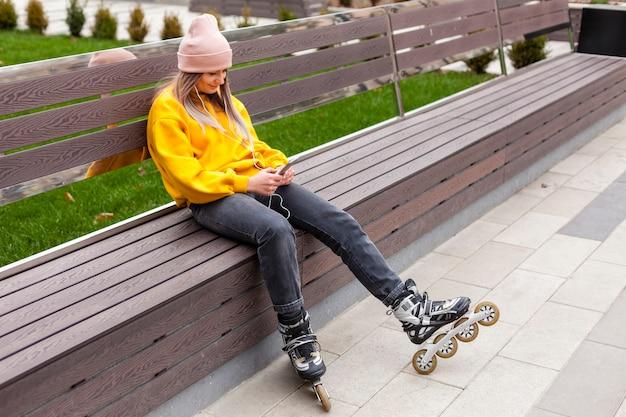 女性がローラーブレードを着用しながらベンチでポーズ 無料写真