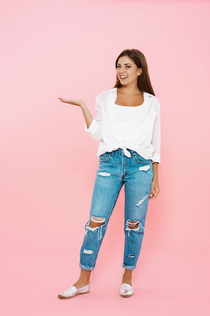Woman posing on pink wall with right hand in air Free Photo