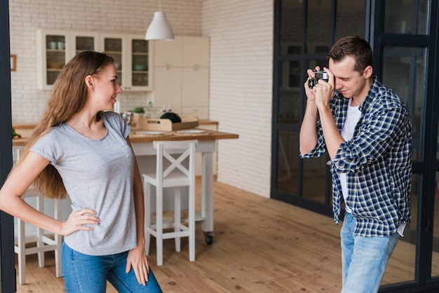 Woman posing for shot while man using photo camera Free Photo