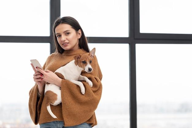 Женщина позирует, держа собаку и смартфон Бесплатные Фотографии