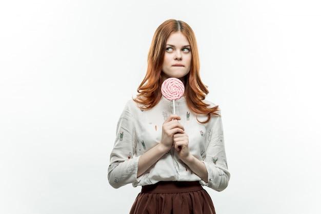 Женщина позирует с леденцом, изолированные стены Premium Фотографии