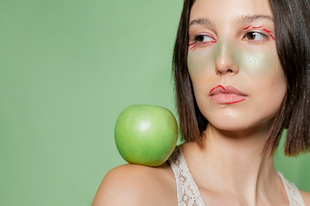 Woman posing with apple on shoulder Free Photo