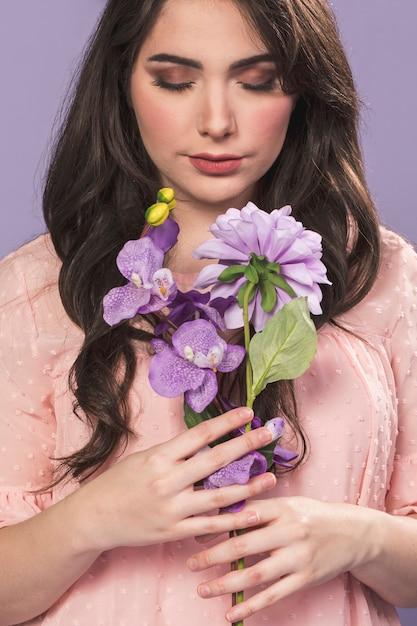 女性が蘭とダリアの花束でポーズ 無料写真