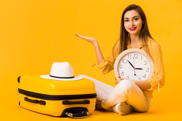 Woman posing with clock in hand next to luggage with hat on top Free Photo