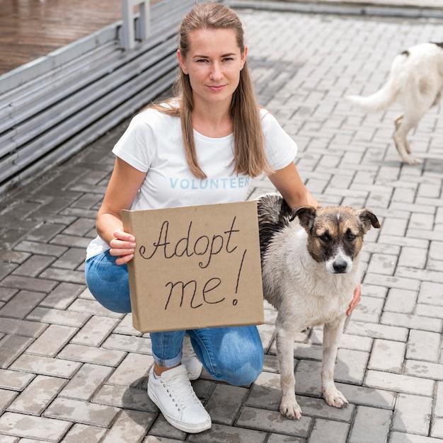 Женщина позирует с собакой и держит знак усыновить меня для домашнего животного Бесплатные Фотографии