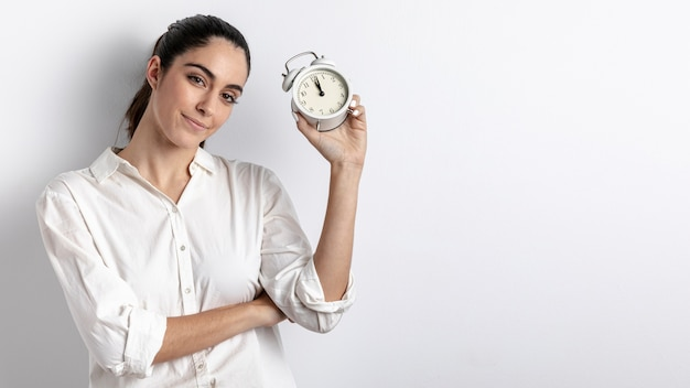 Woman posing with hand held clock and copy space Free Photo
